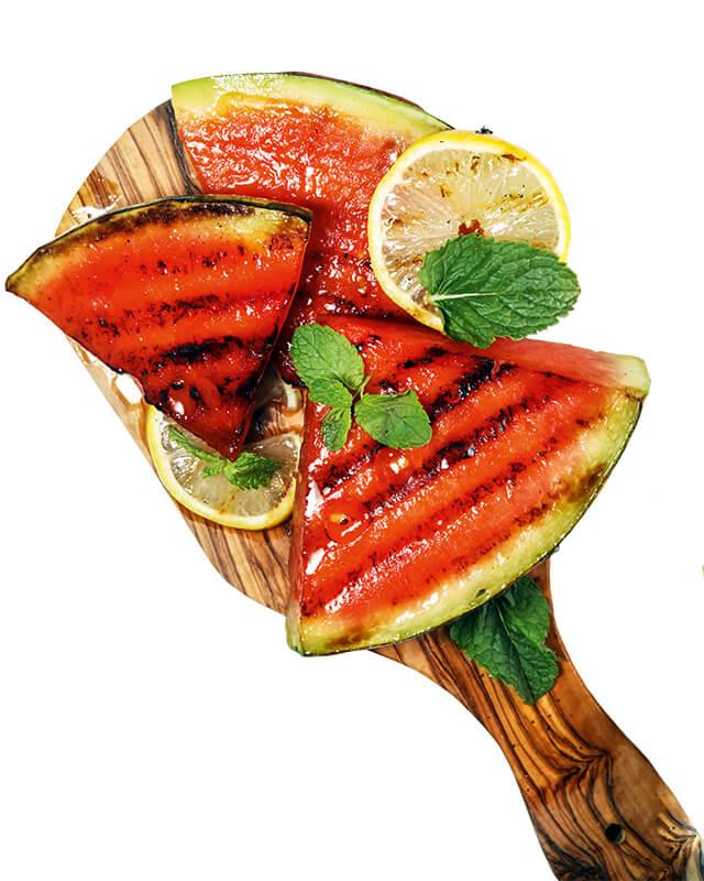 gegrillte Melonenstücke auf Holzlöffel arrangiert (verweist auf: Köstliche Kugeln – Melonen in vielen Varianten)