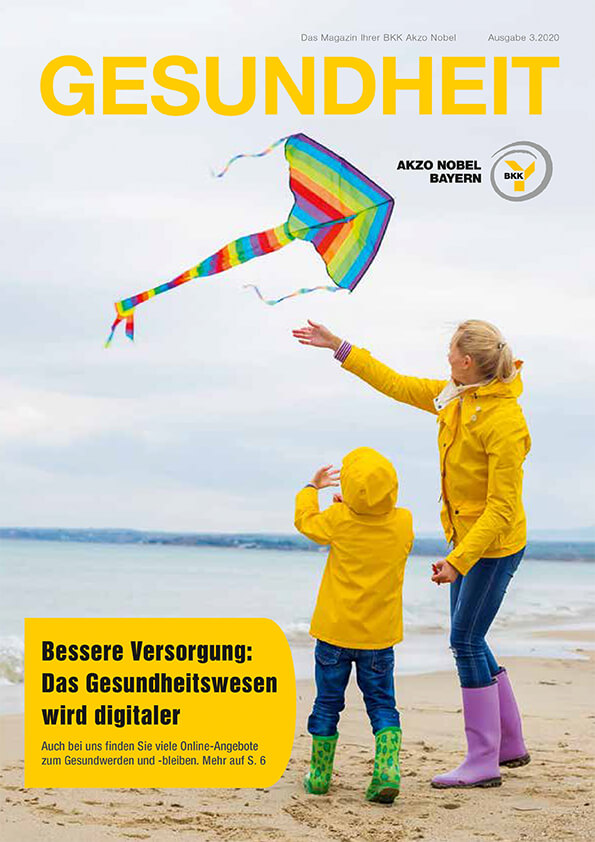 Mutter und Kind lassen Drachen am Strand steigen