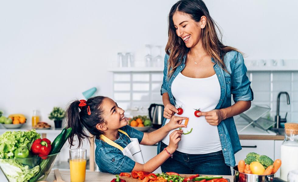 Schwangere Frau und Tochter vor gesunden Lebensmitteln in der Küche