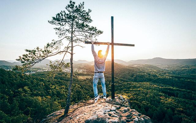 Junger Mann am Gipfelkreuz